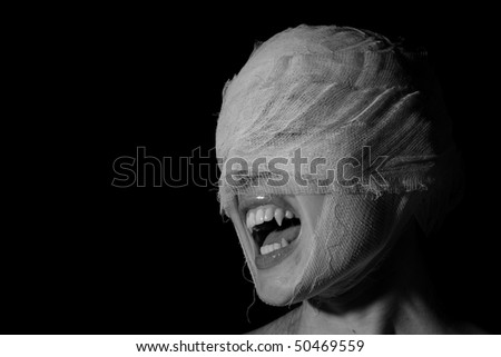Girl's face wound with bandage with a teeth as at the vampire on a black background