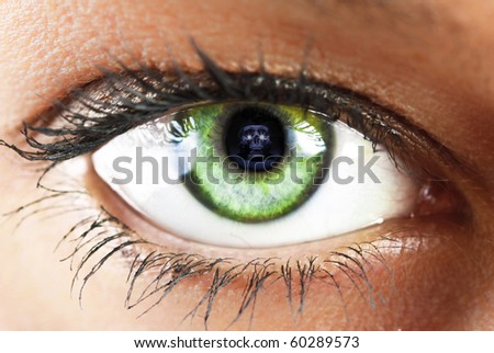 girl's green eye close up with skull reflected - stock photo