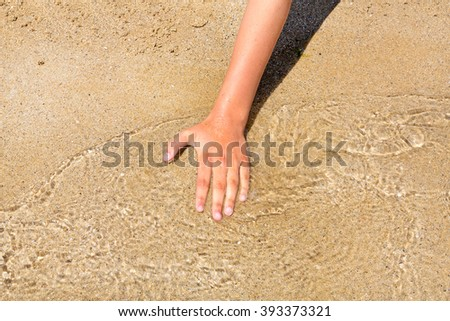 Girl's hand catches a wave on the shore