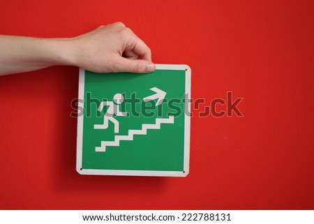 Girl's hand holding a green exit sign along red wall - stock photo