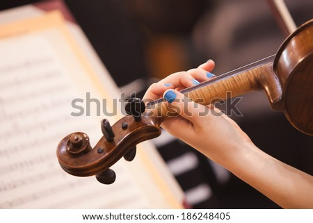Girl's hand on the fingerboard violin - stock photo