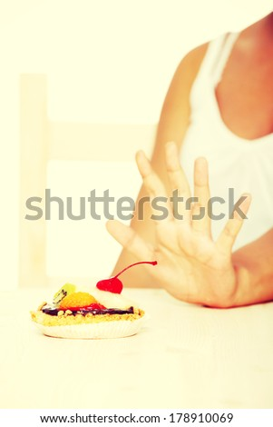 girl`s hand showing stop gesture to cake.