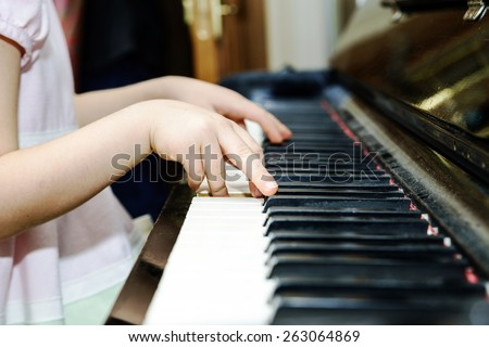 Girl's hands and piano keyboard close-up view, education concept