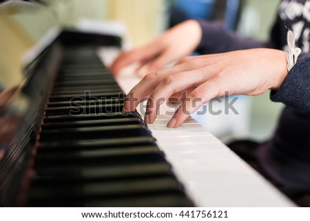 Girl's hands on the keyboard of the piano. playing the piano