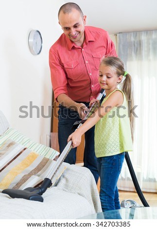 girl 5s helping father to do regular clean-up indoors