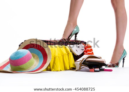 Girl's leg on filled suitcase. Hat near closed filled suitcase. Luggage for trip is ready. Never too much clothing. - stock photo