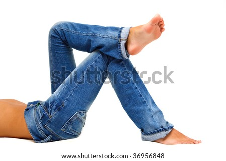 Girl's legs in a blue jeans over white - stock photo