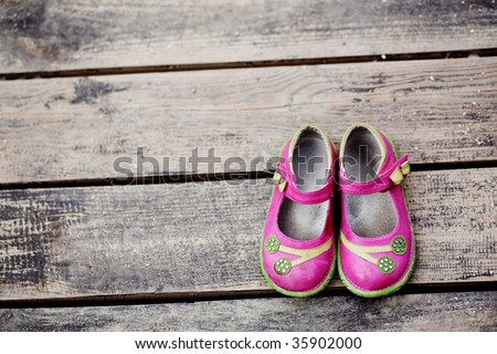 Girl's small shoes on wood - stock photo