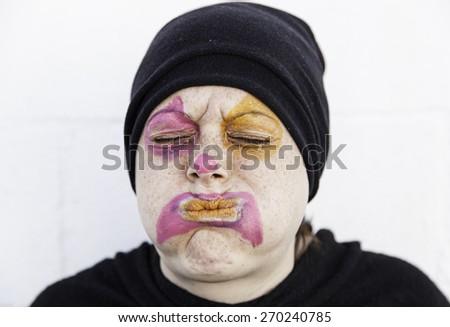 Girl sad clown in urban street, expression - stock photo