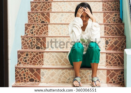 girl sad sitting alone at staircase in the park,focus hand - stock photo
