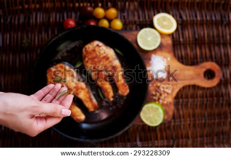 Girl salts Two red fish steak fried in a frying pan for two persons, is a pan on a wooden board close tomatoes and slices of lemon and lime - stock photo