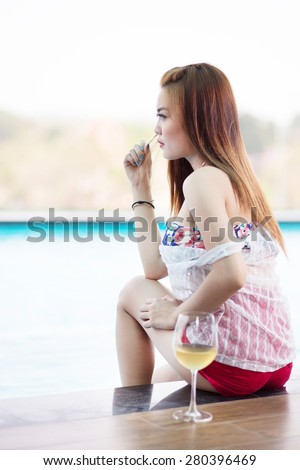 Girl sat staring happily drink by the swimming pool with monochrome color. - stock photo