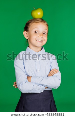 Girl school girl in a school uniform with a green apple on his head and her hand crossed. Learning and school concept. Image on chromakey background. - stock photo