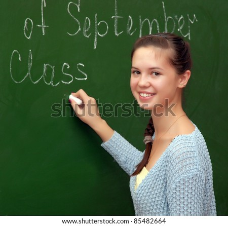 Girl schoolgirl meets an English lesson on the background of the school boards - stock photo