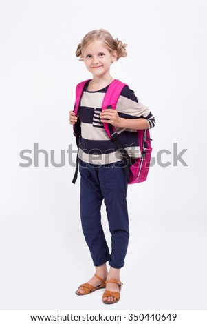Girl schoolgirl on a white background with a backpack and books in hands looking at the camera.