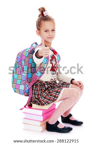 Girl schoolgirl sitting on a stack of books behind her schoolbag satchel-isolated on white background - stock photo