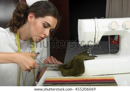 Girl seamstress cutting fabric with scissors. On her neck hangs a ribbon tape measure