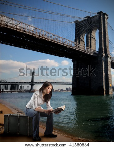 girl seated on suitcase reading book and bridge of brooklyn on the background - stock photo