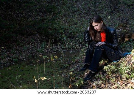 Girl seating near pond in thw forest