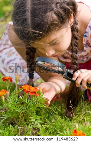 girl sees flowers through magnifying glass - stock photo