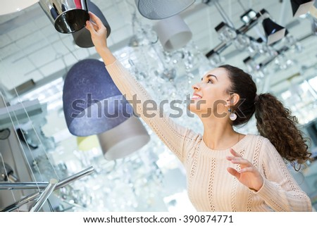 Girl selecting chandelier for interior in household store