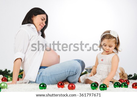 girl selecting marker for drawing on mother's belly - stock photo