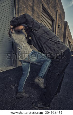 GIRL SELF DEFENSE | A young woman defends herself against a male attacker in an alley. Refuse to be a victim.    - stock photo