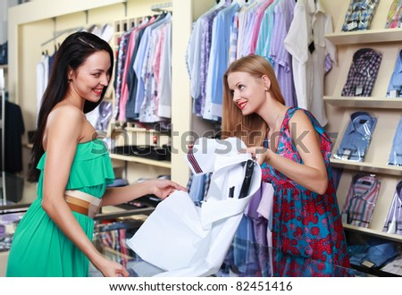 Girl seller helps shoppers choose the clothes in the store - stock photo
