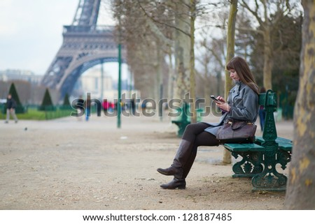 Girl sending sms or surfing in the net in Paris - stock photo
