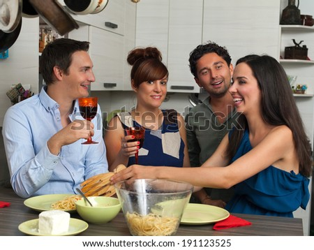 Girl serving pasta to her friends - stock photo