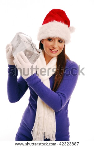 Girl shaking christmas present to guess what it is - stock photo