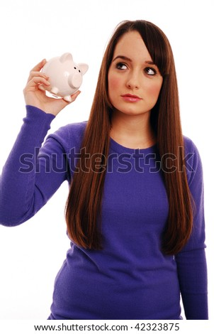 Girl shaking to piggy bank - stock photo