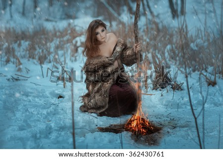 Girl shaman is heated by the fire in winter in the forest. Blizzard sweeps, and it is snowing. - stock photo