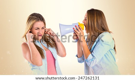 Girl shoutimg with a megaphone at her friend - stock photo