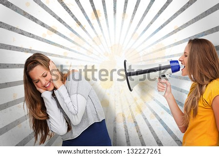 Girl shouting at her friend through megaphone on grey and white linear pattern - stock photo