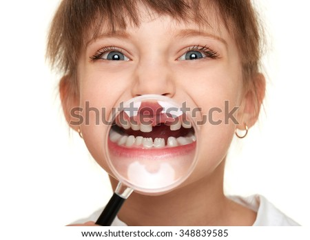 girl show lost tooth through magnifying glass - stock photo