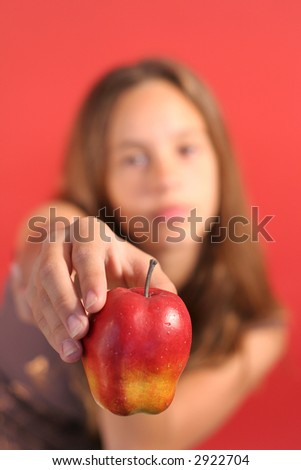 girl showing apple (focus on apple)