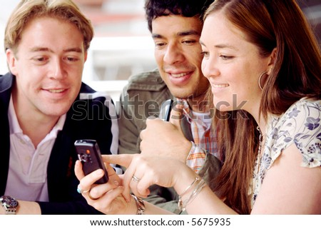 girl showing her mobile phone to her friends at a restaurant - stock photo