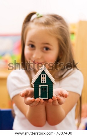 Girl showing her wish to their parents: a new home [focus on the house] - stock photo
