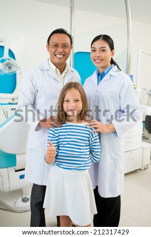 Girl showing thumbs-up while standing with dental team - stock photo