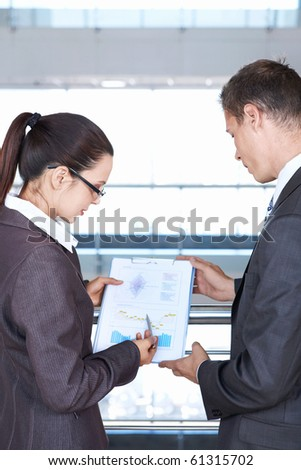 Girl shows a colleague sales chart - stock photo