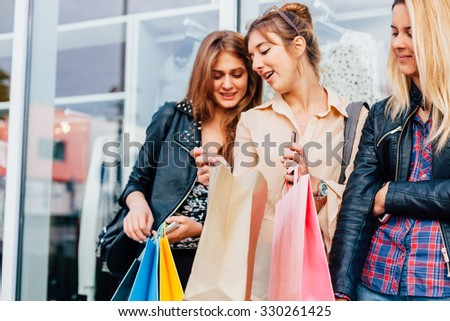 Girl shows her friends her shopping bag after purchasing - stock photo