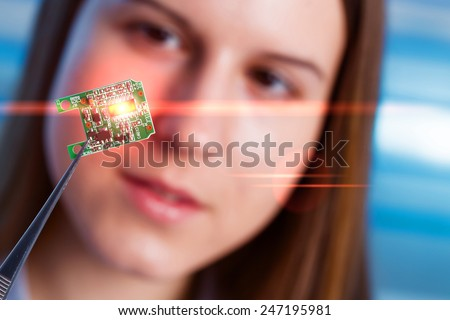 Girl shows new microchip on plate  that can be implanted into a paralyzed patient, developed a microchip muscle simulator - stock photo