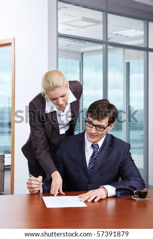 Girl shows the boss where to put the signature - stock photo
