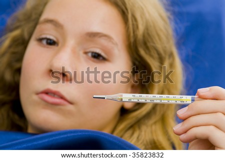 girl sick in bed, having over 39?C /102?F fever. with a shallow depth of field - focus on thermometer.