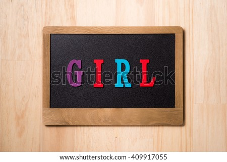 Girl sign on blackboard on a wooden background - stock photo