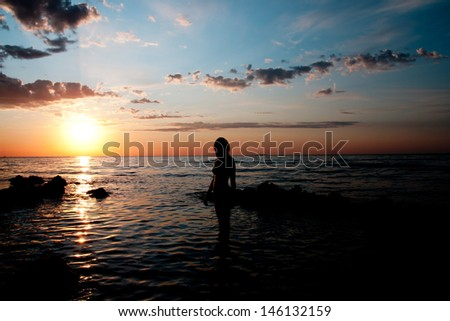 girl silhouette at sunset of the sea background