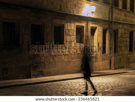 Girl silhouette in motion on night illuminated street in Europe  - stock photo