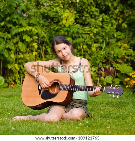 Girl singing and playing the guitar outdoors - stock photo