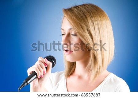Girl singing with microphone against gradient background - stock photo